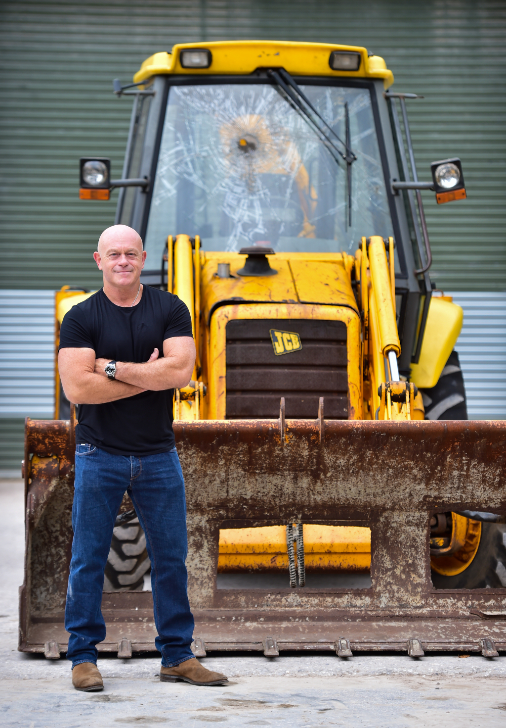 Ross Kemp pictured during his visit to JCB with the backhoe  loader used by the Millennium Dome raiders